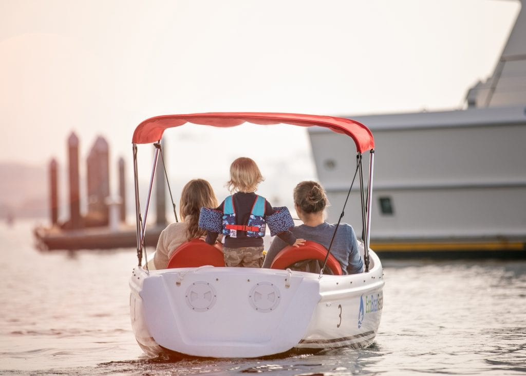 Family pedaling on an Eco boat rental